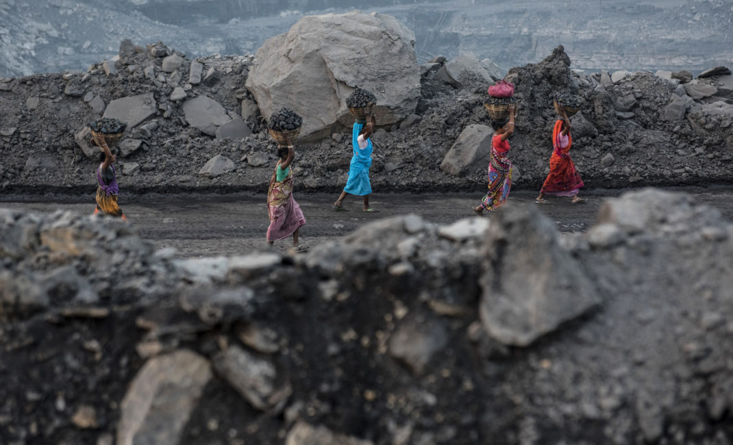 Women come back from the mine carrying baskets full of coal