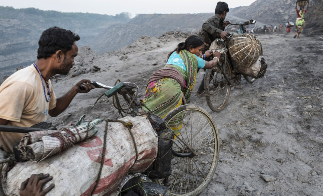 """Coal cycle-wallahs"" push bicycles loaded with bags of coal along the road"