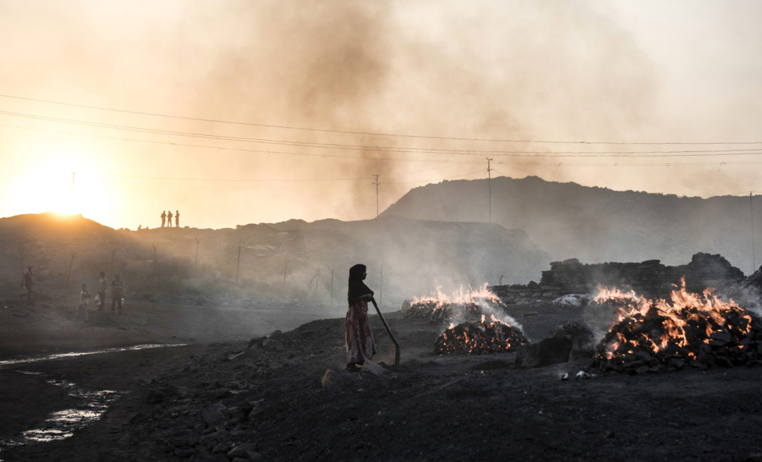 A girl stands among fires in Kusunda village