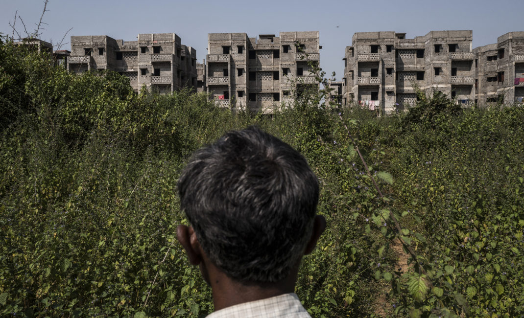 A man stands in front of a housing complex in Belgaria, where Jharia's working class has been relocated