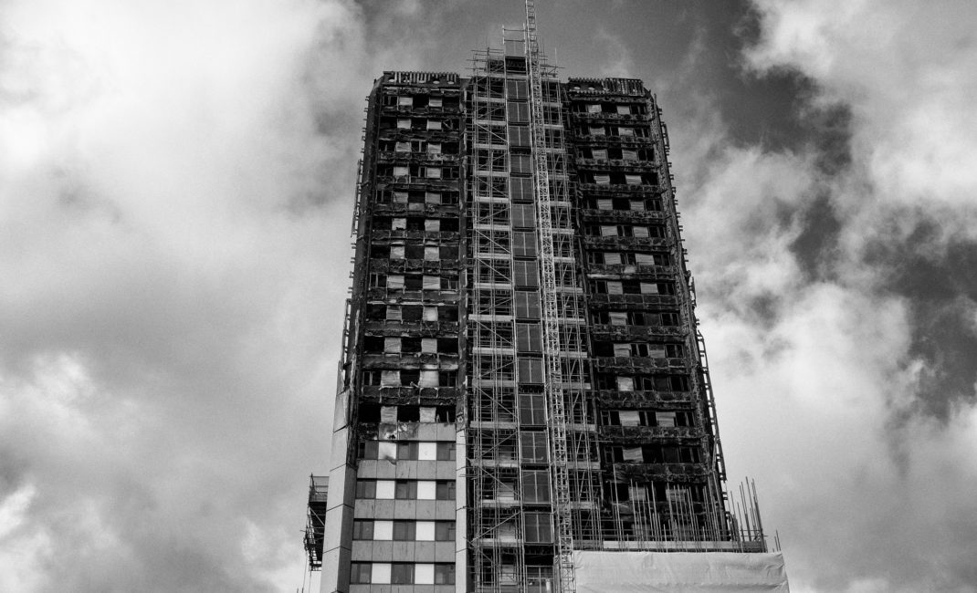 A black and white photograph looking up at the burnt shell of Grenfell Tower.