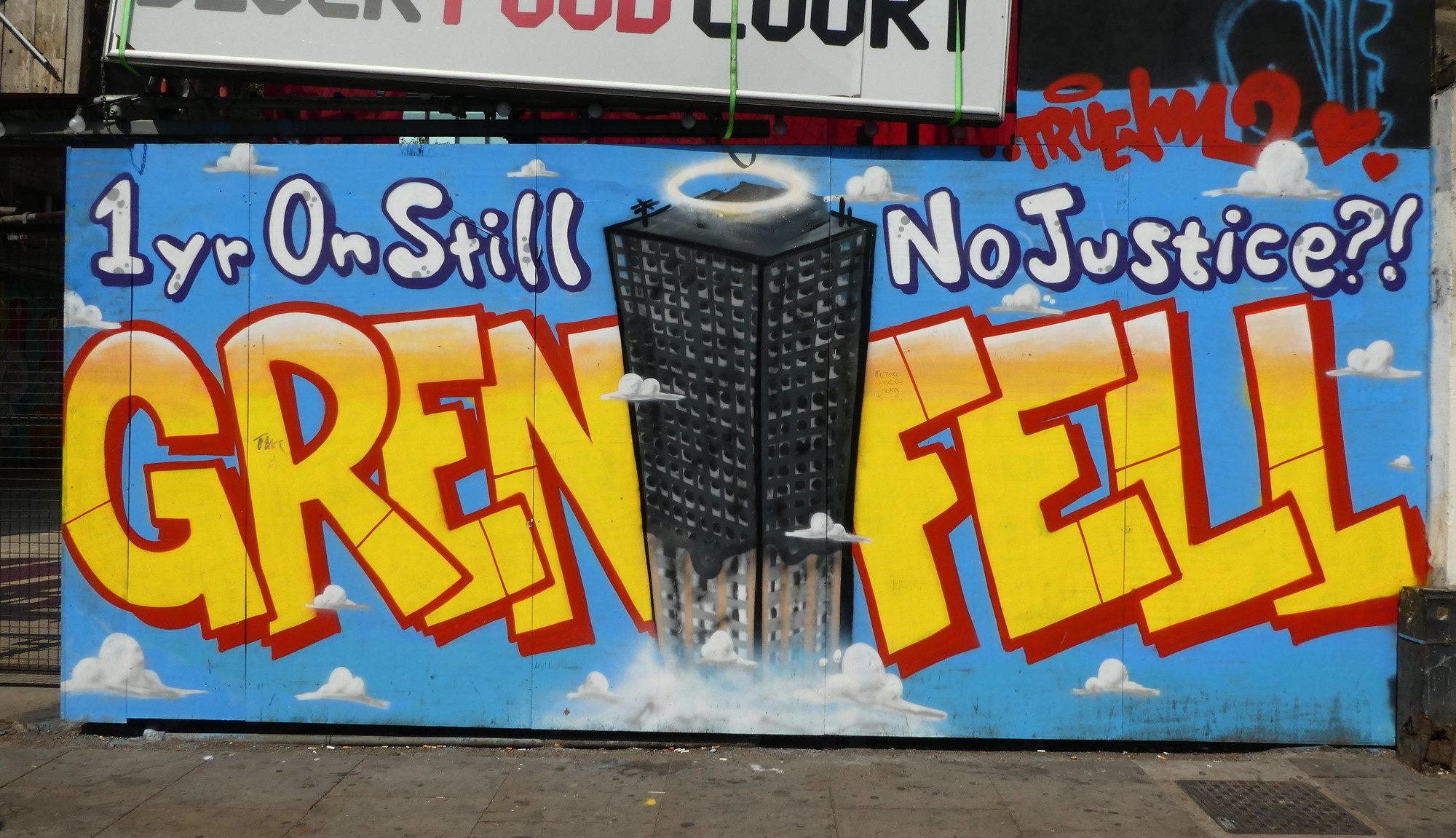 "Graffiti reads ""Grenfell - One year on still no justice?!"""