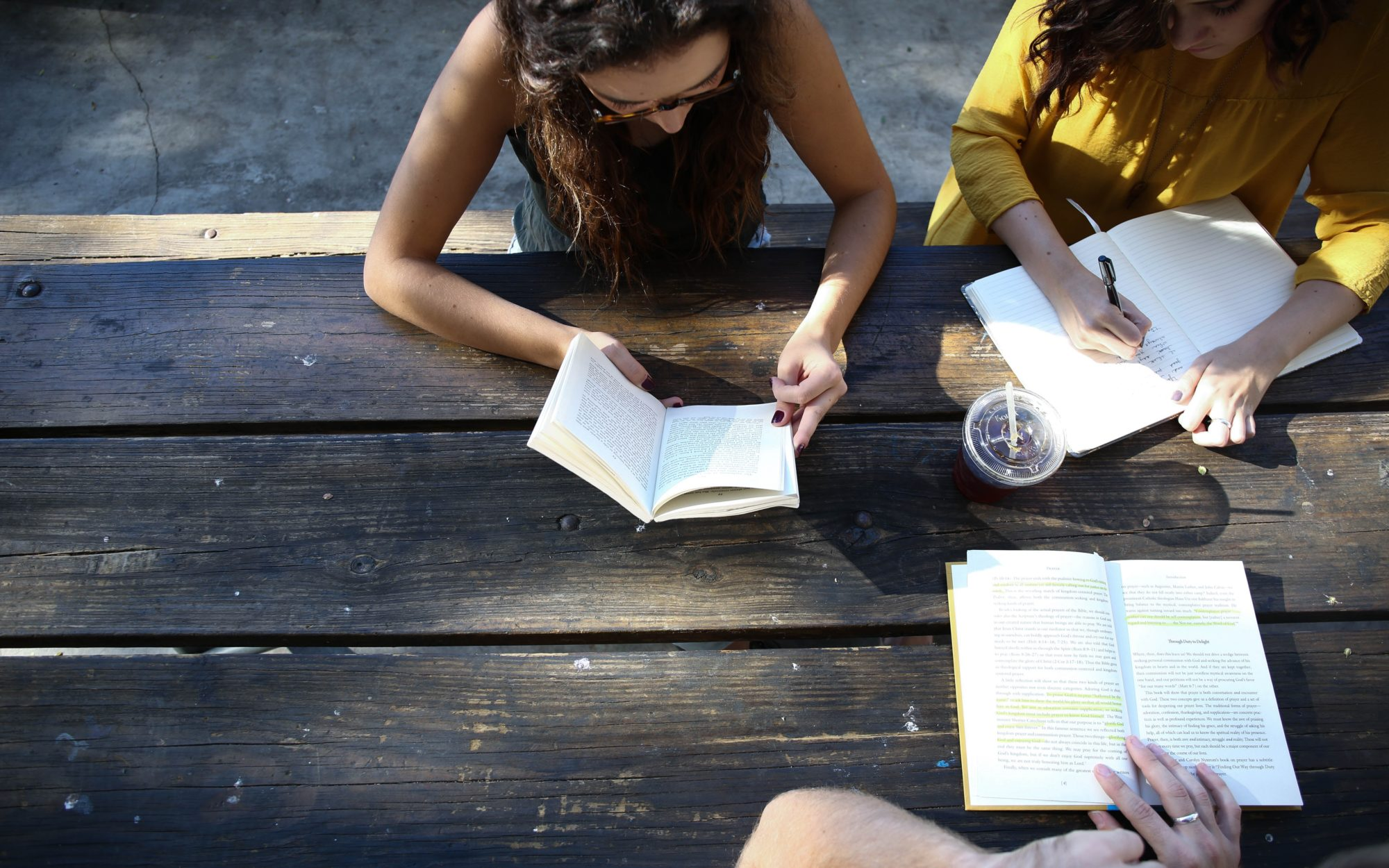 Three girls writing in separate notepads on a bench outdoors