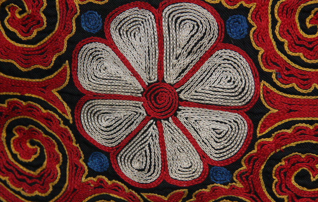 A white rose outlined in red in a Kazakh tapestry