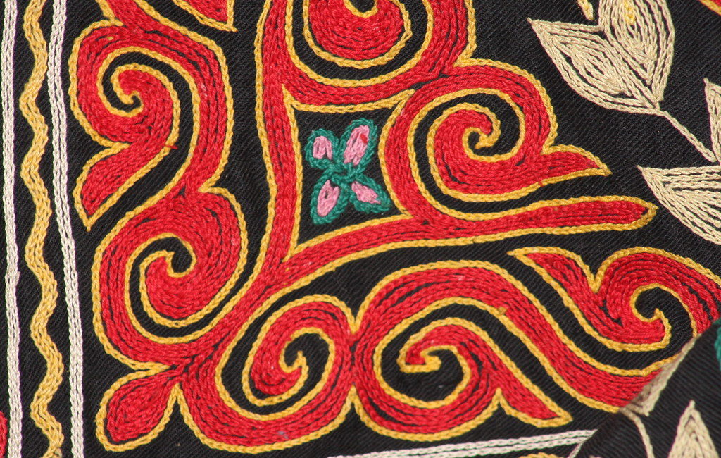 A swirling pattern of red and gold thread in a Kazakh tapestry