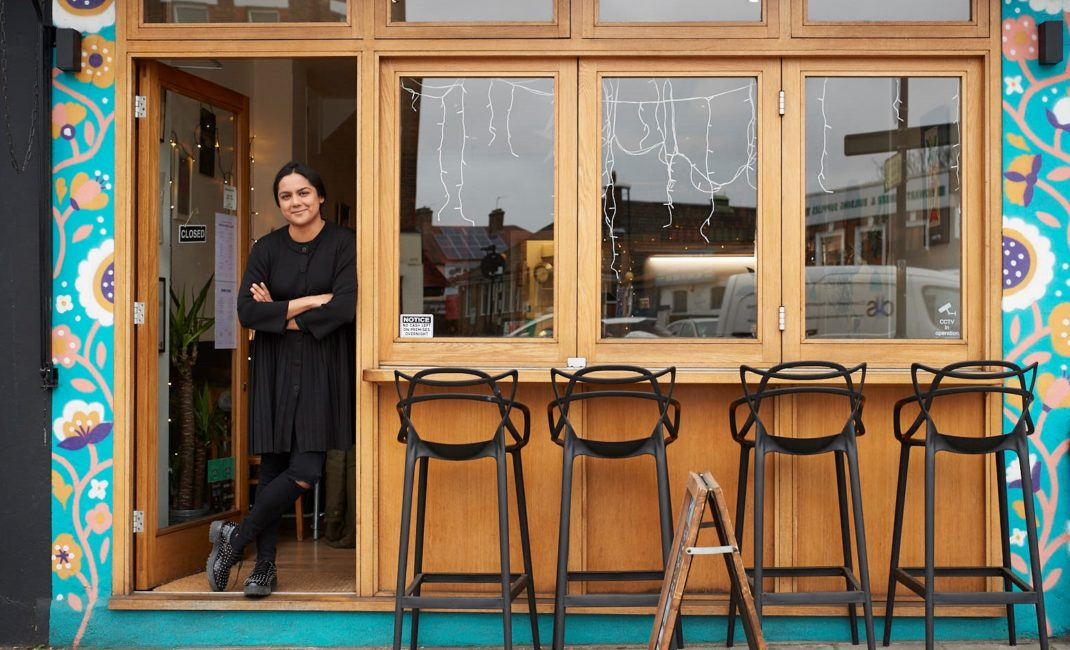 Saima Thompson leans with her arms folded in the wooden doorway of her restaurant Masala Wala Cafe