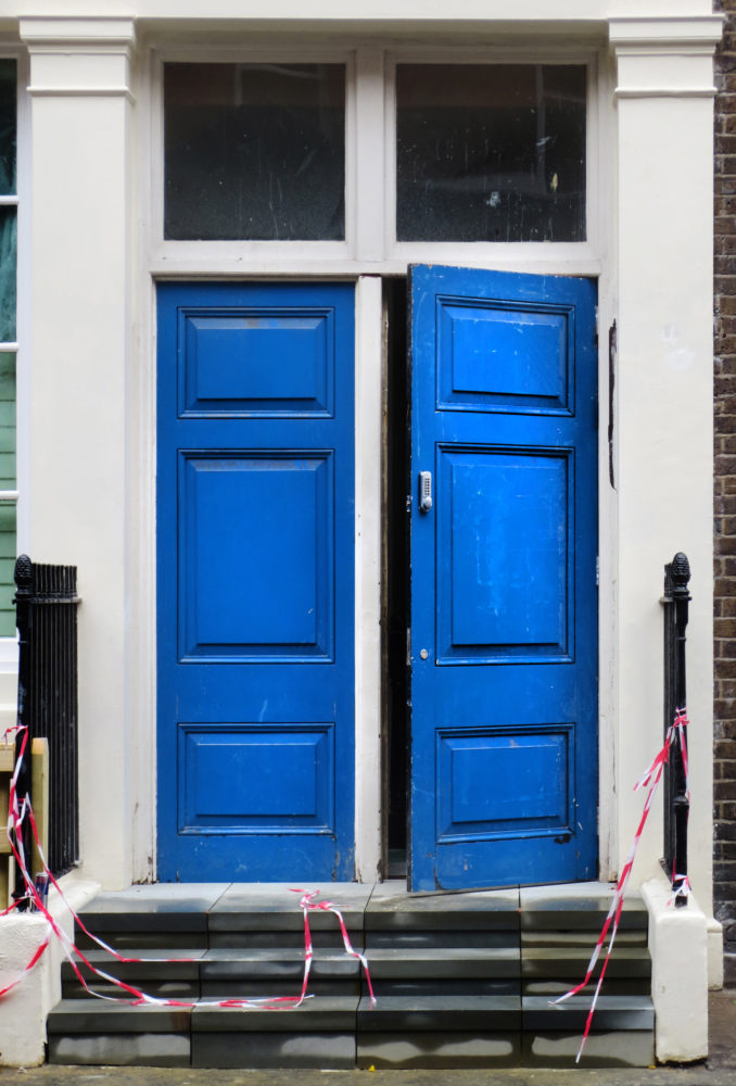 Photograph of bright blue double doors with steps in front
