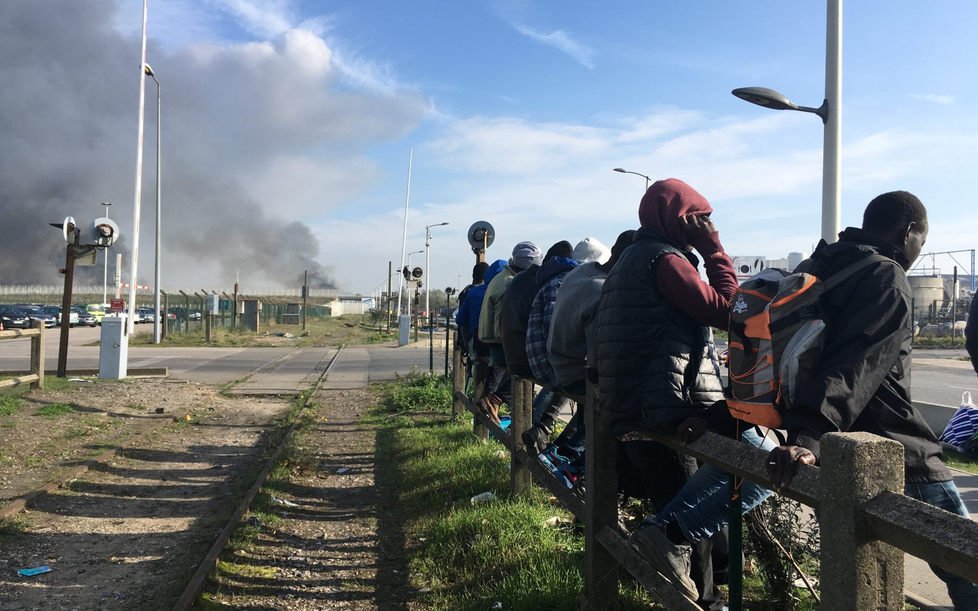 It Can Be Done migrant law podcast - a row of refugee men sitting on a fence by a railway track