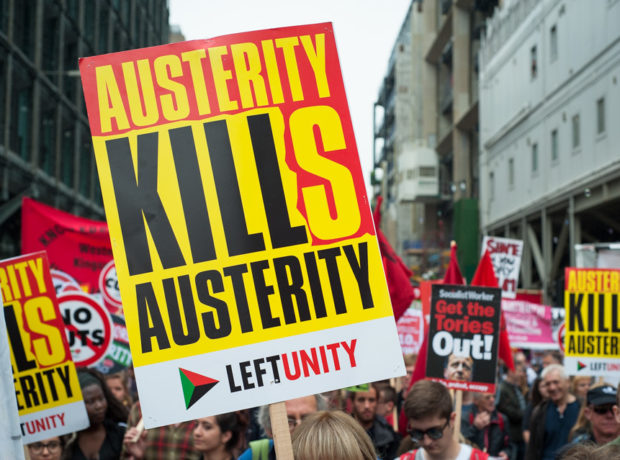 "End Austerity ""Austerity Kills"" placard carried at a street protest"