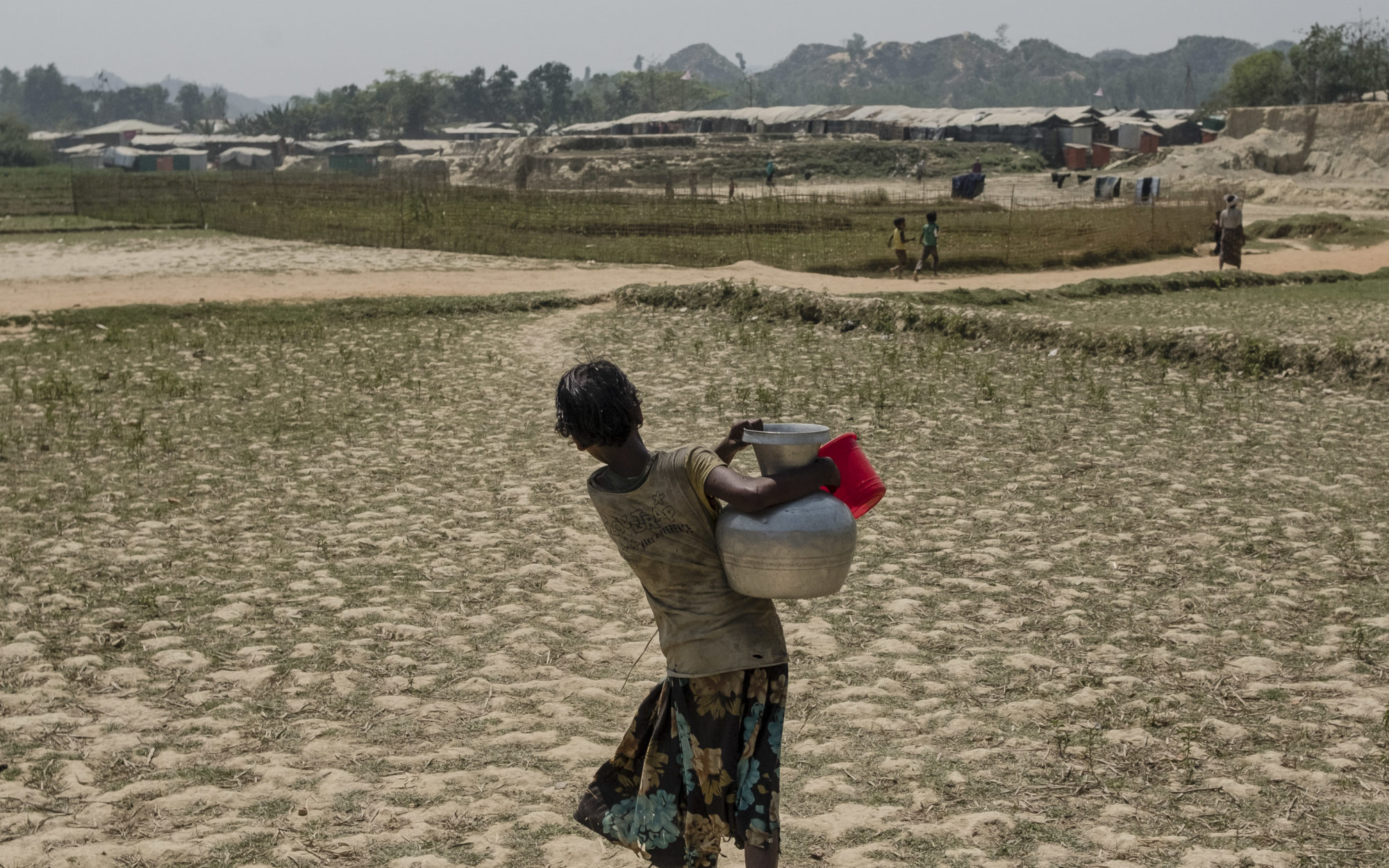 A Rohingya girl carries water to her camp