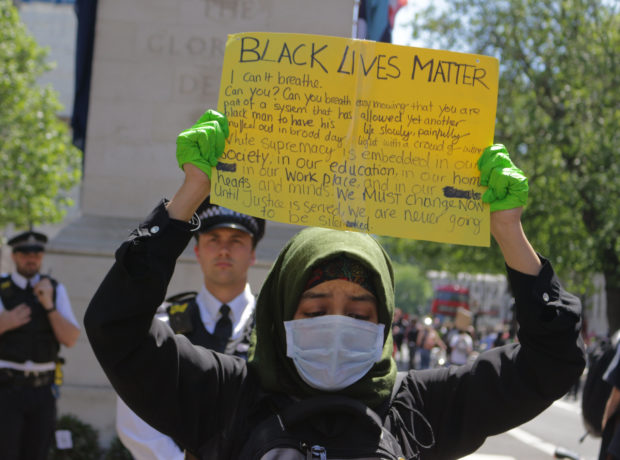 Black Lives Matter protest in London May 2020, a young Muslim woman, wearing a hijab, a face mask and green surgical gloves, looks down as she lifts a homemade BLM placard