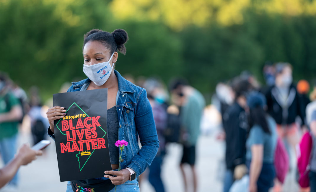 George Floyd vigil at the Lincoln Memorial - a young Black woman wears a face mask and holds a Black Lives Matter poster