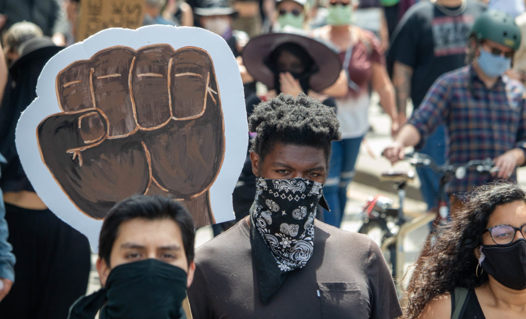 Protesters in face masks walk beside a giant power fist placard in George Floyd Black Lives Matter protest in Eugene, Oregon