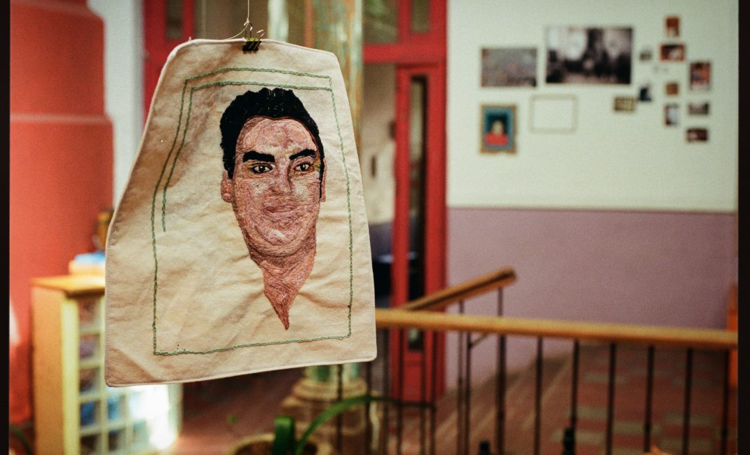 Members of <em>Familiares Caminando por Justicia</em> (Families Walking for Justice) embroider faces of missing people on white fabrics - by Mauricio Ramirez de Anda
