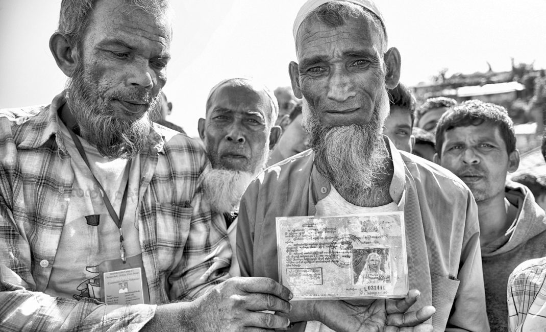 1.A group of refugees in the Jamtoli refugee camp showing their Myanmar citizenship cards. Although some of the elderly refugees have citizenship ID, the government of Myanmar has long considered the Rohingya as foreign citizens, greatly challenging any repatriation negotiations.