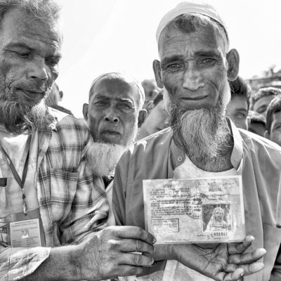 1. A group of refugees in the Jamtoli refugee camp showing their Myanmar citizenship cards. Although some of the elderly refugees have citizenship ID, the government of Myanmar has long considered the Rohingya as foreign citizens, greatly challenging any repatriation negotiations.