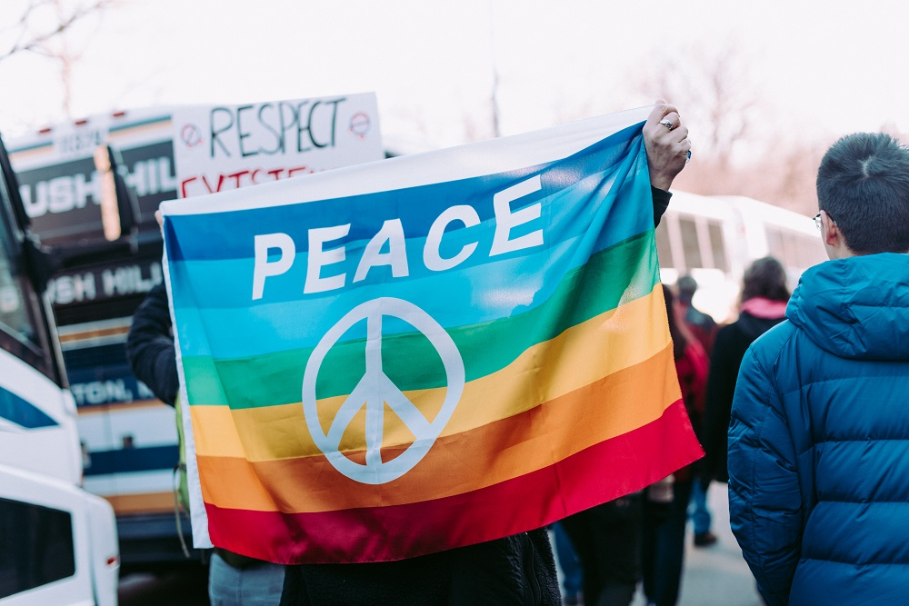 A rainbow-coloured flag bearing the word PEACE and a peace sign is carried in a crowd of people