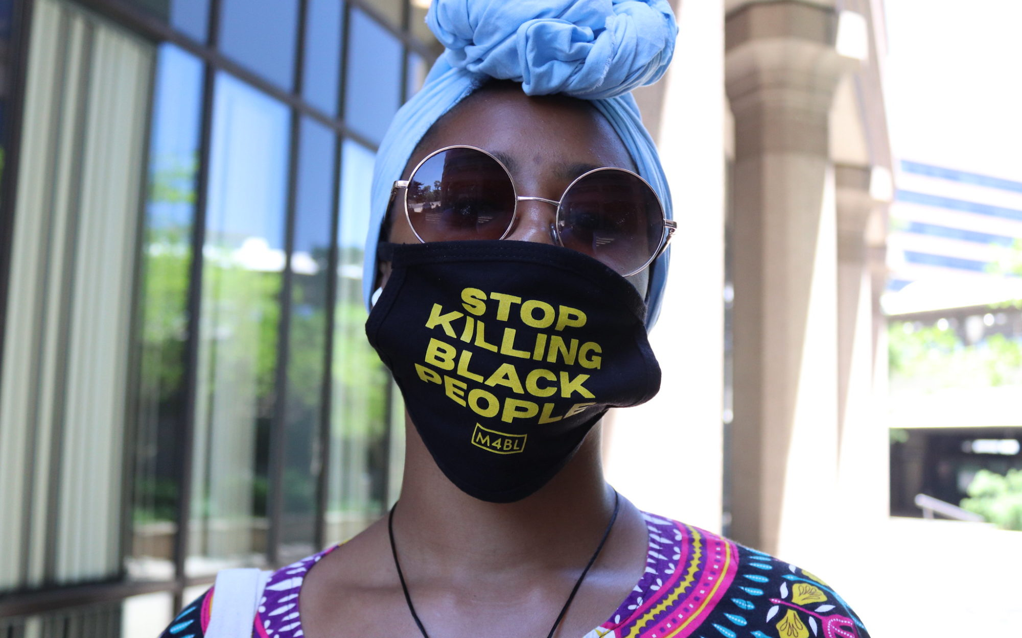 Black woman wearing a 'Stop Killing Black People' mask. Demonstrates that even withing a global pandemic, black people are fighting for their lives everyday