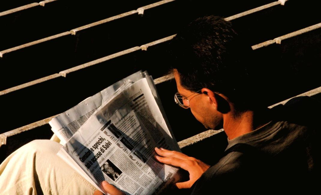 A man reads an Italian newspaper in the sunshine