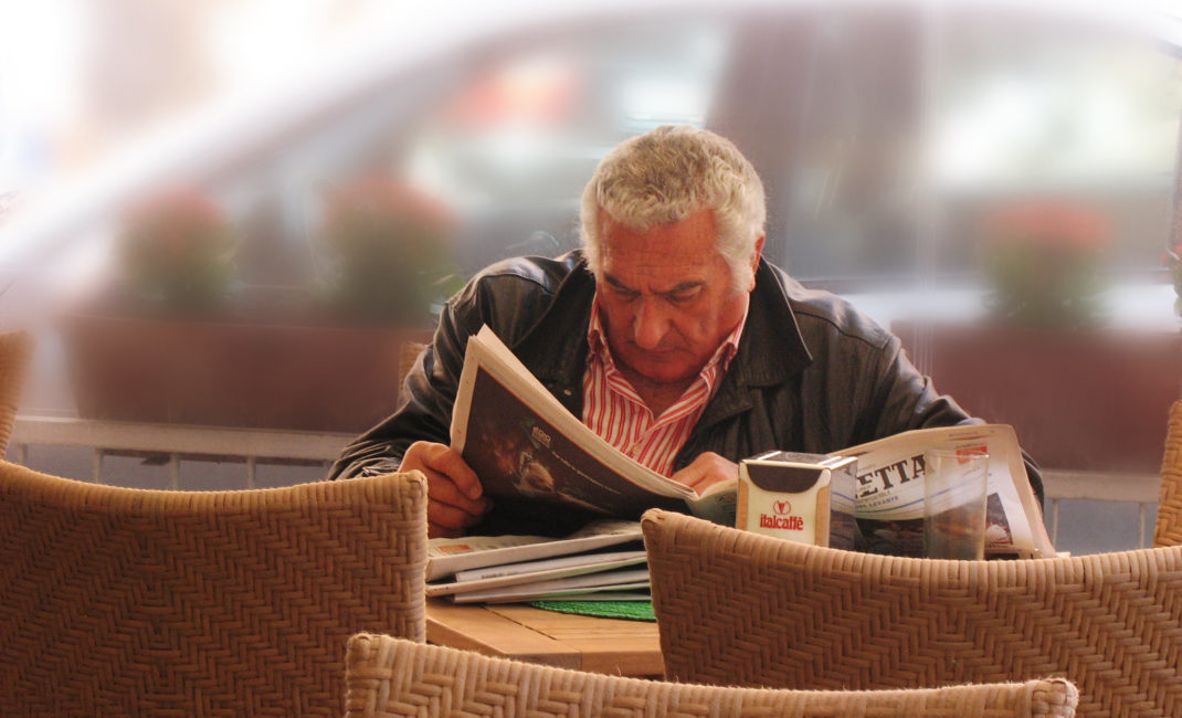 A man reads an Italian newspaper in a cafe