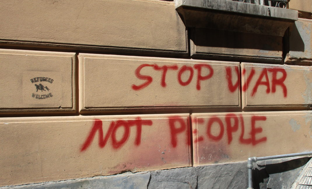 """Red graffiti on a yellow wall reads: """"STOP WAR NOT PEOPLE"""""""
