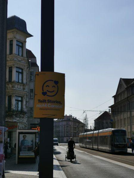 "A yellow street sign in Leipzig reads: ""Teilt Stories, nicht Corona"" (Share stories, not Corona)"