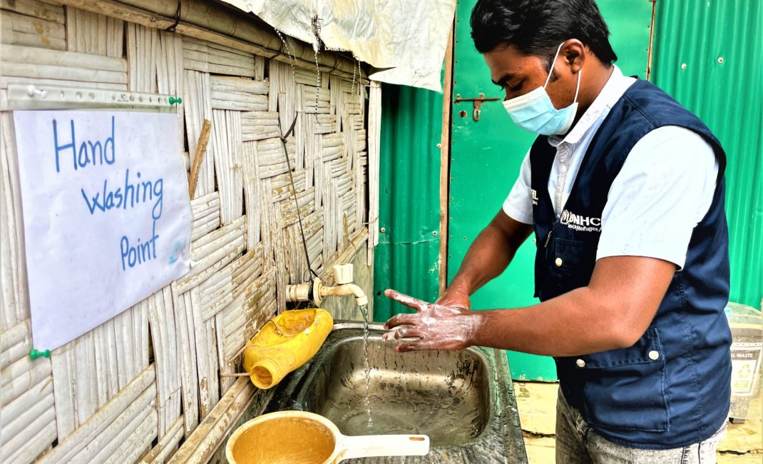 Mohammad Jaber, a UNHCR Covid health volunteer, wears a face mask and washes his hands
