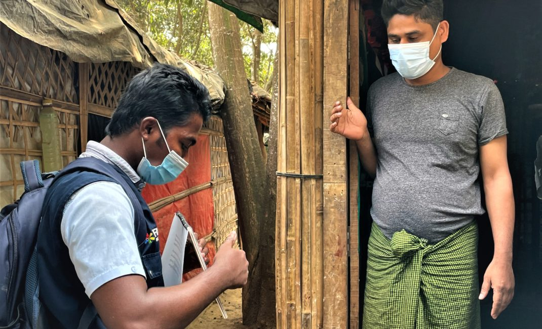 Mohammad Jaber, a UNHCR Covid health volunteer in Rohingya refugee camps, wears a face mask and points to health advice on a notepad for a man standing in a doorway