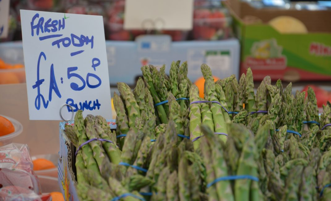 """Bunches of freshly picked asparagus on sale at market next to sign: """"Fresh today - £1.50 bunch"""""""