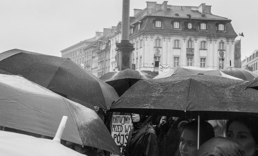 Black and white photo of women marching under many umbrellas in the Black Protests in Poland